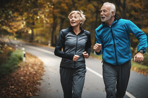 Closeup front view of a senior couple jogging in a forest and having fun. They are running on a winding forest road, laughing and doing their healthy routine. They are looking sideways to the left.