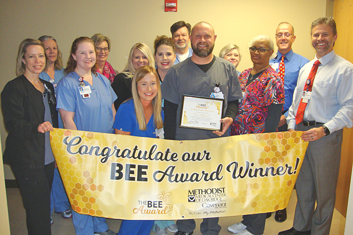 BEE Award Honoree Eric Shepard is surrounded by co-workers and leadership during his presentation.