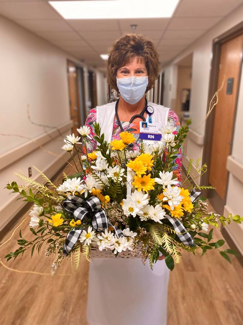 Oncology nurse Tracy Smaron holding her custom-made floral arrangement from her DAISY award presentation.